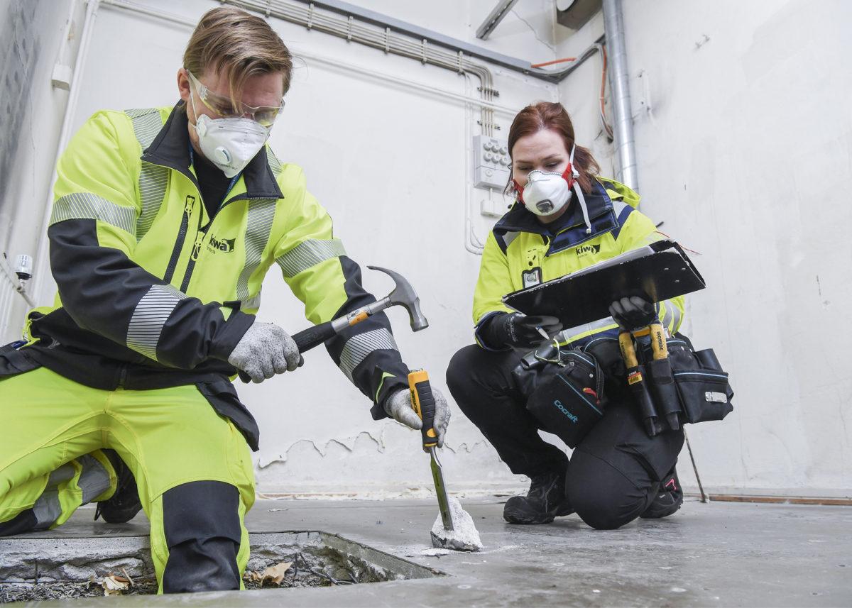 Ville Ruotsalainen nakuttaa lattiasta näytteen, ja Aino Taitto merkitsee sen luetteloon.