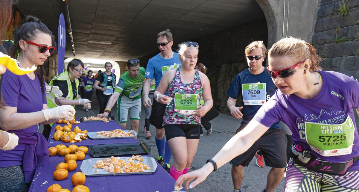 Juoksijat kauhoivat insinöörien tarjoamia mandariineja kesken matkaa Helsinki  City Running Day -tapahtumassa.