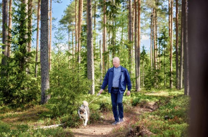 Ari Kettunen rentoutuu metsässä koiraa ulkoiluttamalla.