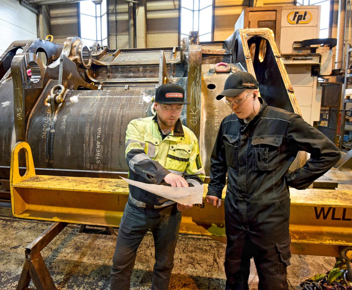 Joonas Sykkö ohjeistaa koneistaja Samu Niemosta suunnittelemansa pistokauhan takaseinän valmistuksessa.