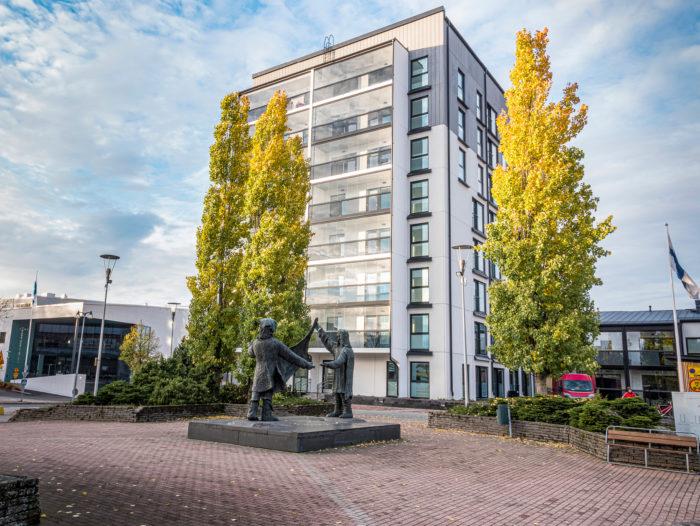 Turkiskauppiaat-patsaan takana on juuri valmistunut kerrostalo ja Virta, kaupungin uusi kirjasto ja kulttuuritalo.