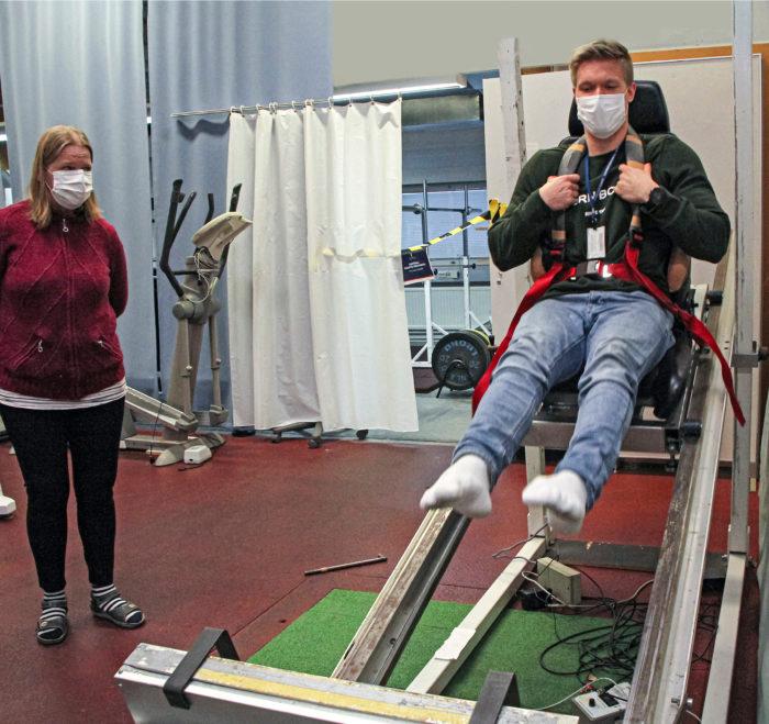 Sirpa Roivas varmistaa ja Sakari Vekki ponnistaa. Kelkalla mitataan lihasvoimaa ponnistuksessa.